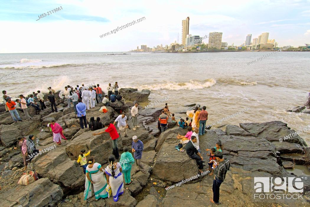 Imagen: indian people enjoy fresh breeze from arabian sea on a rocky area outside the haji ali's mosque and tomb in worli district. mumbay. maharashtra. india.