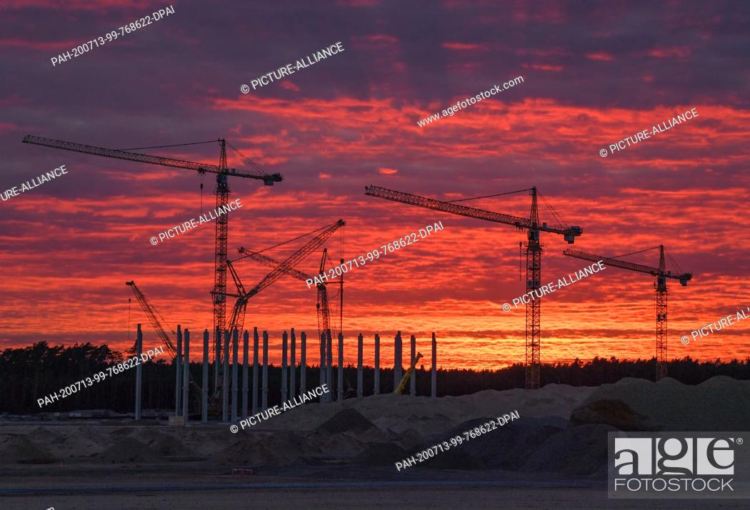 Stock Photo: 12 July 2020, Brandenburg, Grünheide: In front of the colourful sunset, cranes and the first piers for the future Tesla Giga Factory can be seen on the.