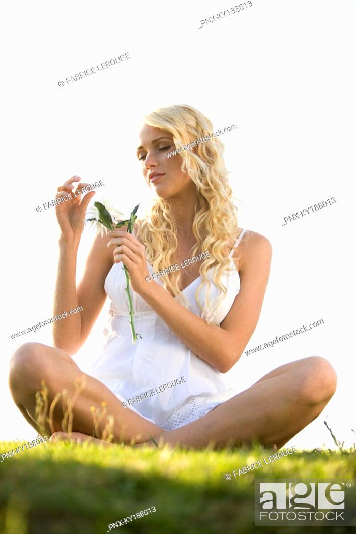 Stock Photo: Young woman holding a flower.
