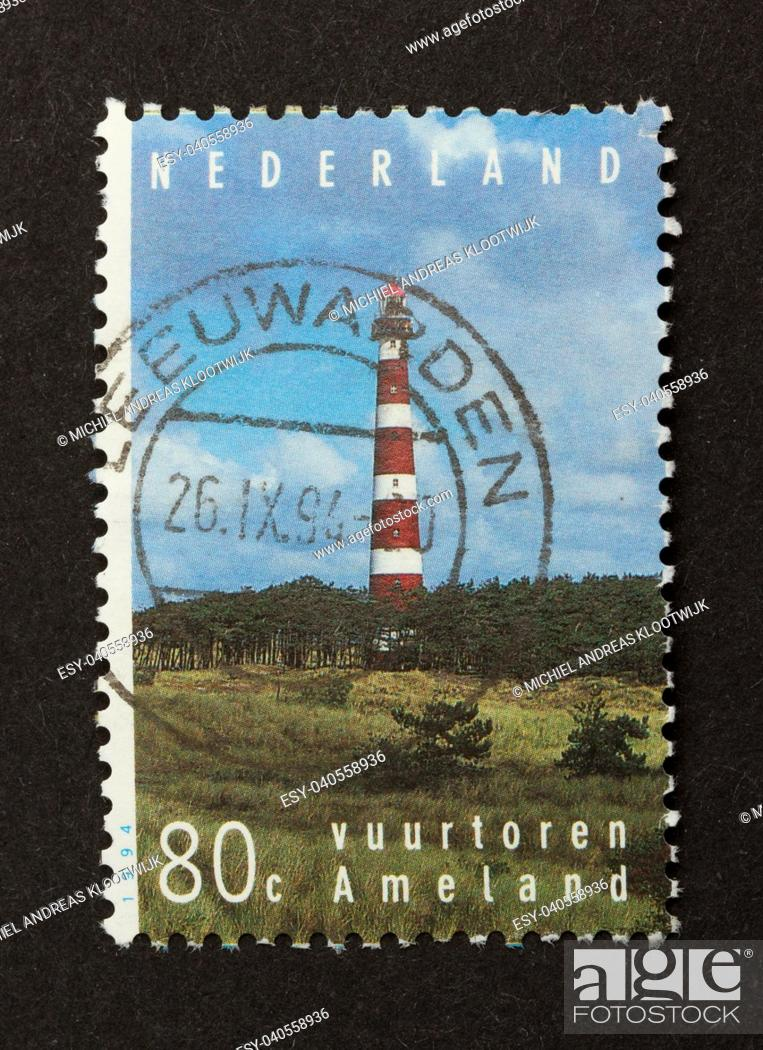 Stock Photo: HOLLAND - CIRCA 1990: Stamp printed in the Netherlands shows the lighthouse of the isle of Ameland, circa 1990.