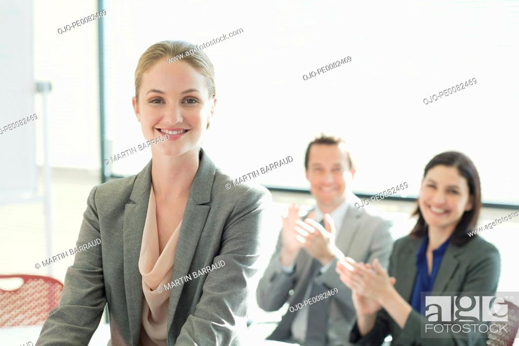 Stock Photo: Co-workers clapping for smiling businesswoman.