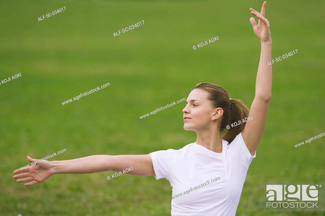 Stock Photo: Young Woman Widely Stretching Arms.