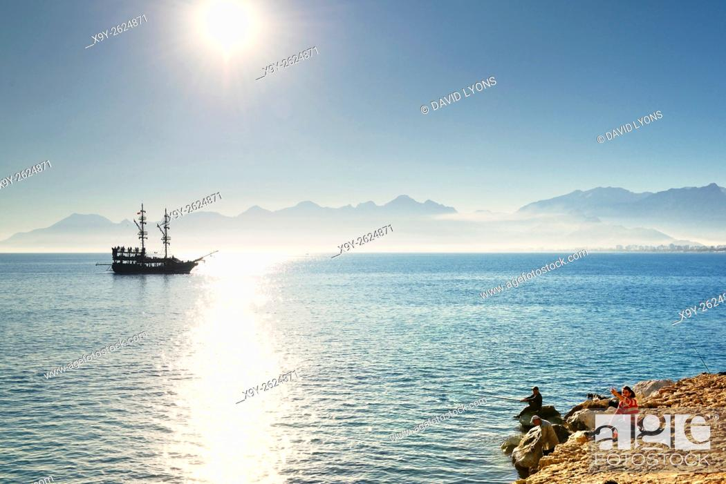 Stock Photo: Antalya, Turkey. Looking west from entrance of Kaleici harbour. Fishermen and tourist sightseeing boat.