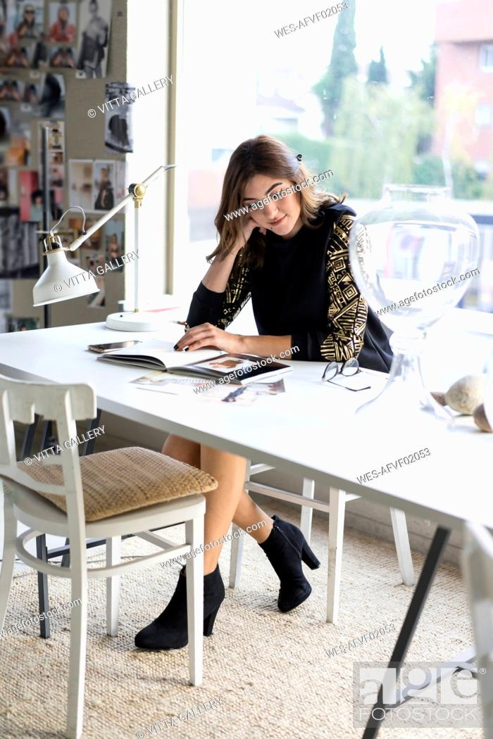 Stock Photo: Young designer watching book in her atelier.