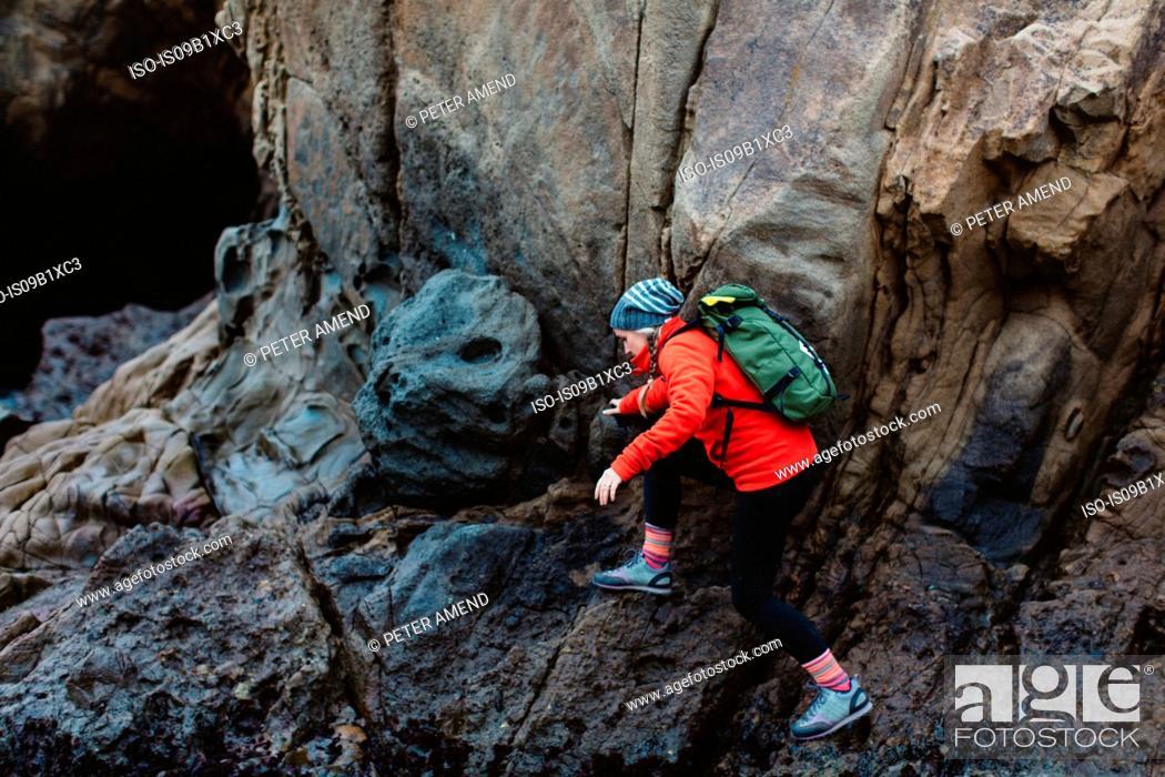 Photo de stock: Hiker climbing over rocks, Big Sur, California, USA.