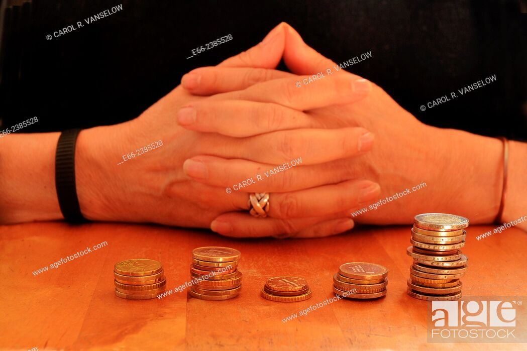 Stock Photo: Woman with hands clasped. Stacks of euro coins in front of her on table.