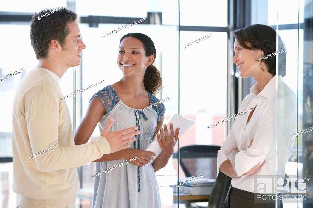 Stock Photo: Three office workers standing in office talking.