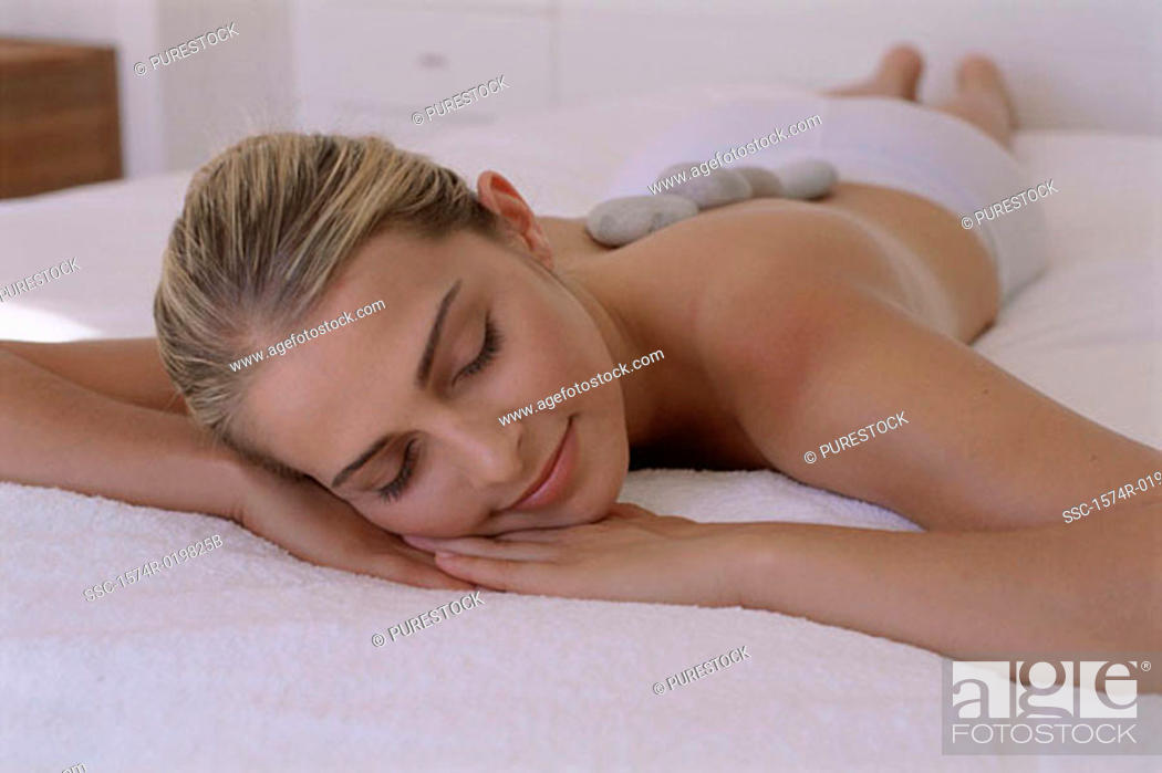 Stock Photo: Close-up of a young woman lying with healing stones on her back.
