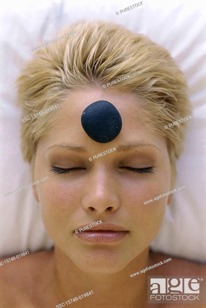 Stock Photo: Young woman with a therapeutic stone on her forehead.