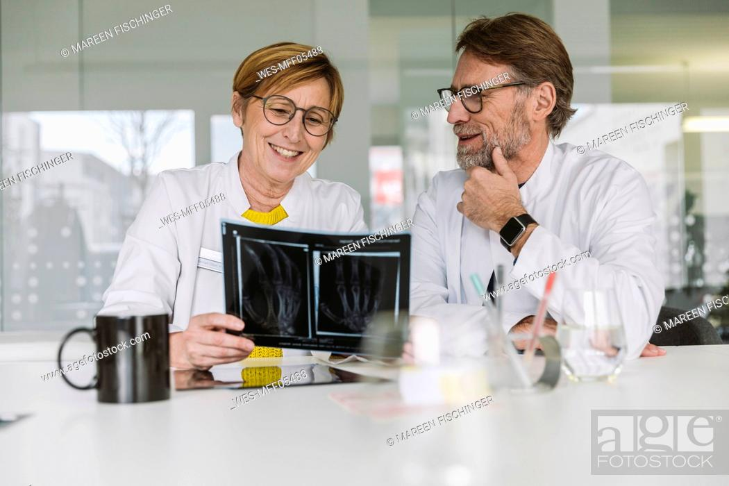 Stock Photo: Two doctors discussing x-ray image of a hand.