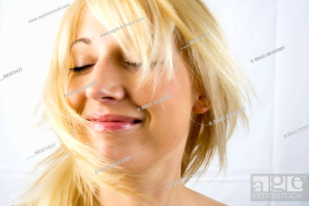 Stock Photo: Young woman model tosses here hair from side to side in studio portrait, Los Angeles, California, USA.