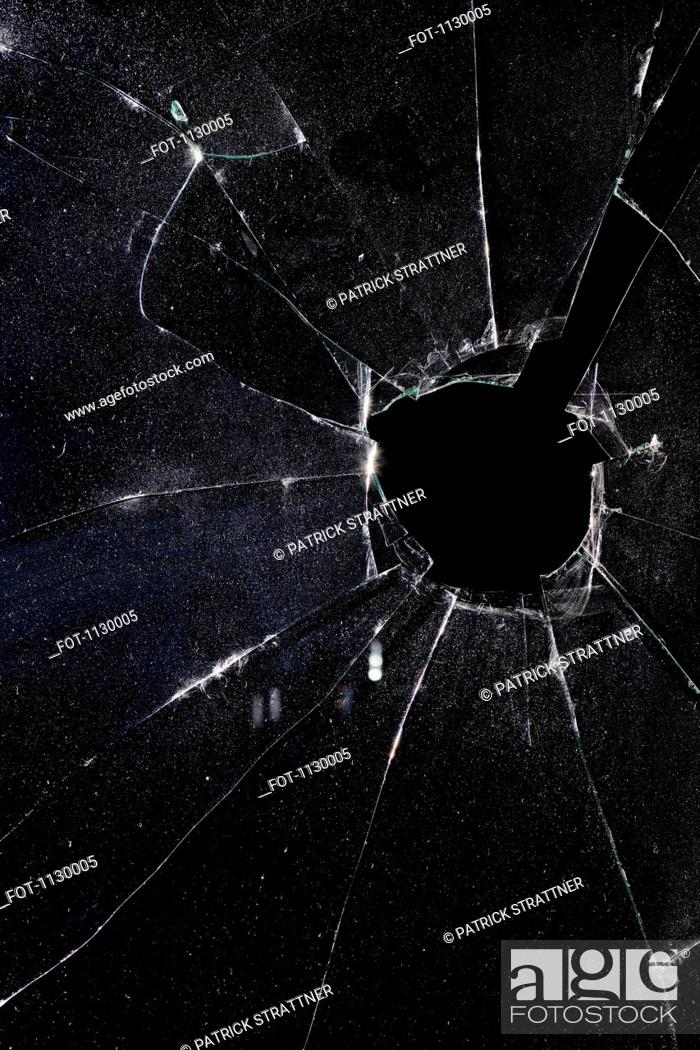 Stock Photo: A window with a hole broken through the glass, night.