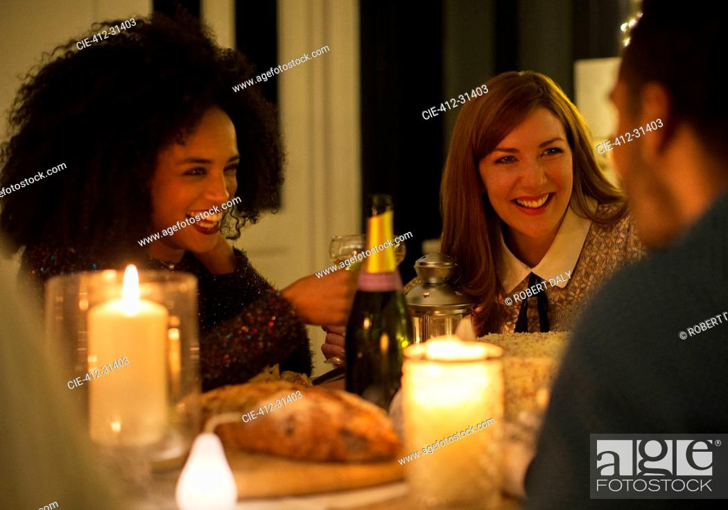 Stock Photo: Smiling friends drinking champagne at candlelight dinner table.