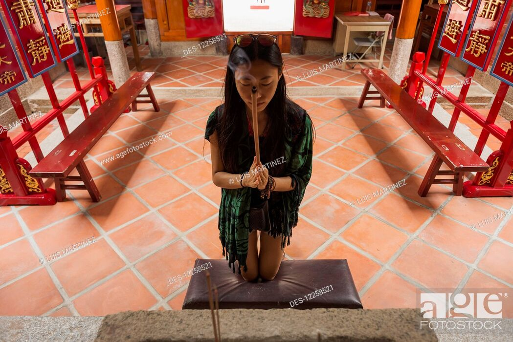 Imagen: A Chinese young woman praying and offering incense in a Buddhist temple; Shanzidou, Kinmen Island, Taiwan.