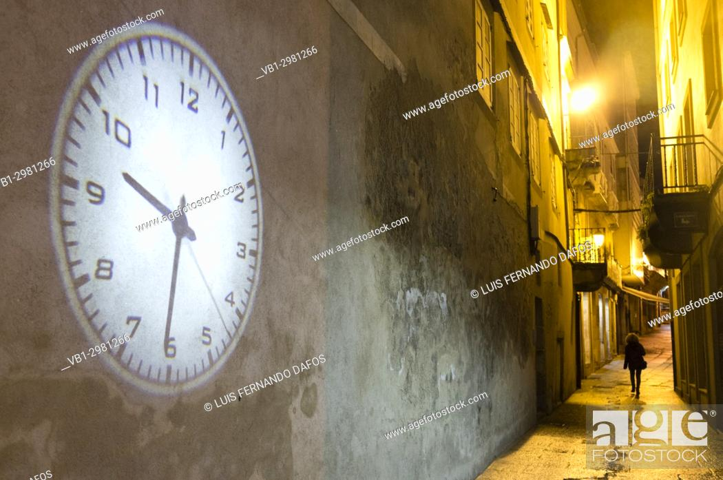 Stock Photo: Lone woman walking on a dark alley and projection of big clock on an empty wall. Old Town of Viveiro, Lugo province, Galicia, Spain, Europe.