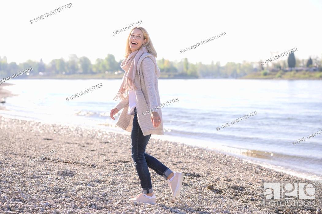 Stock Photo: Happy mature woman walking at the riverside.