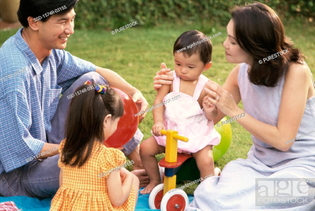 Stock Photo: Parents sitting with their two daughters in a park.