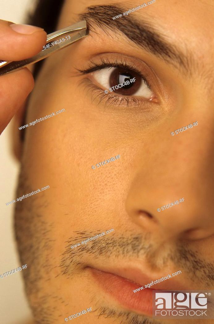 Stock Photo: Man plugging his Eyebrow with Tweezers - Vanity - Beauty.