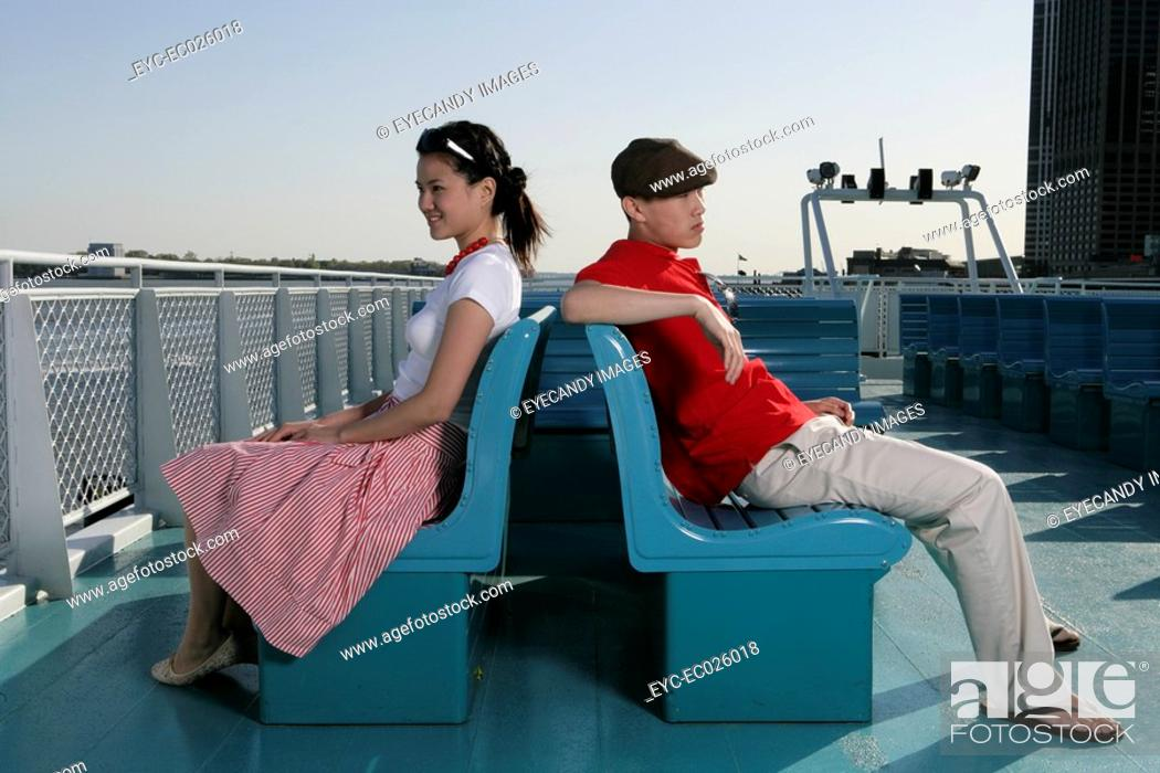 Stock Photo: Two people sitting back to back.