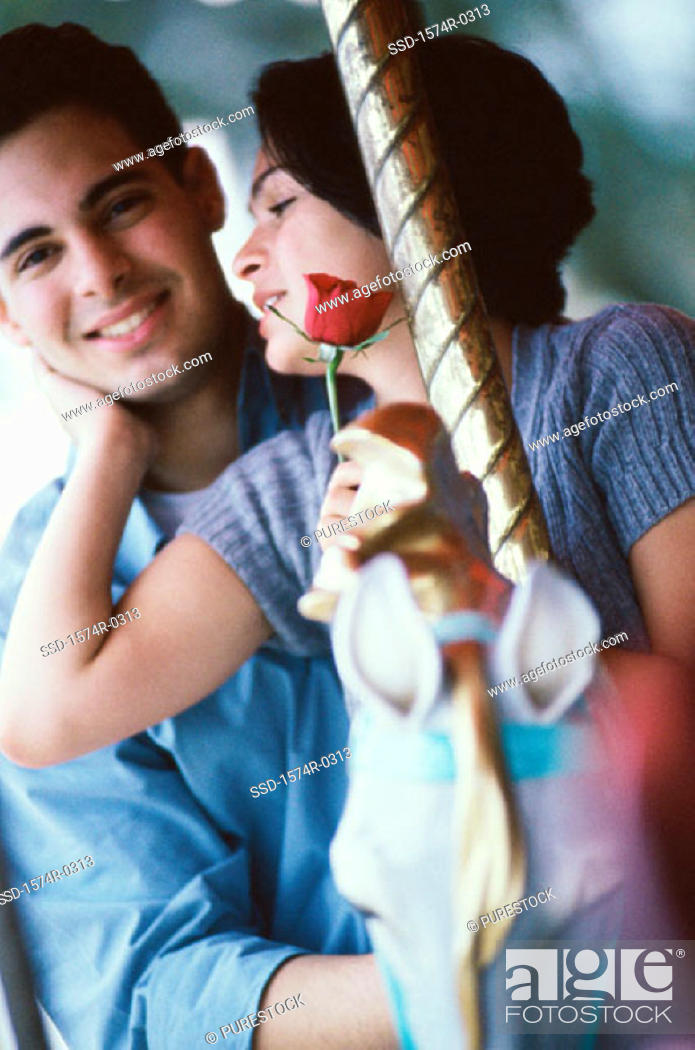 Stock Photo: Young couple riding on a carousel.
