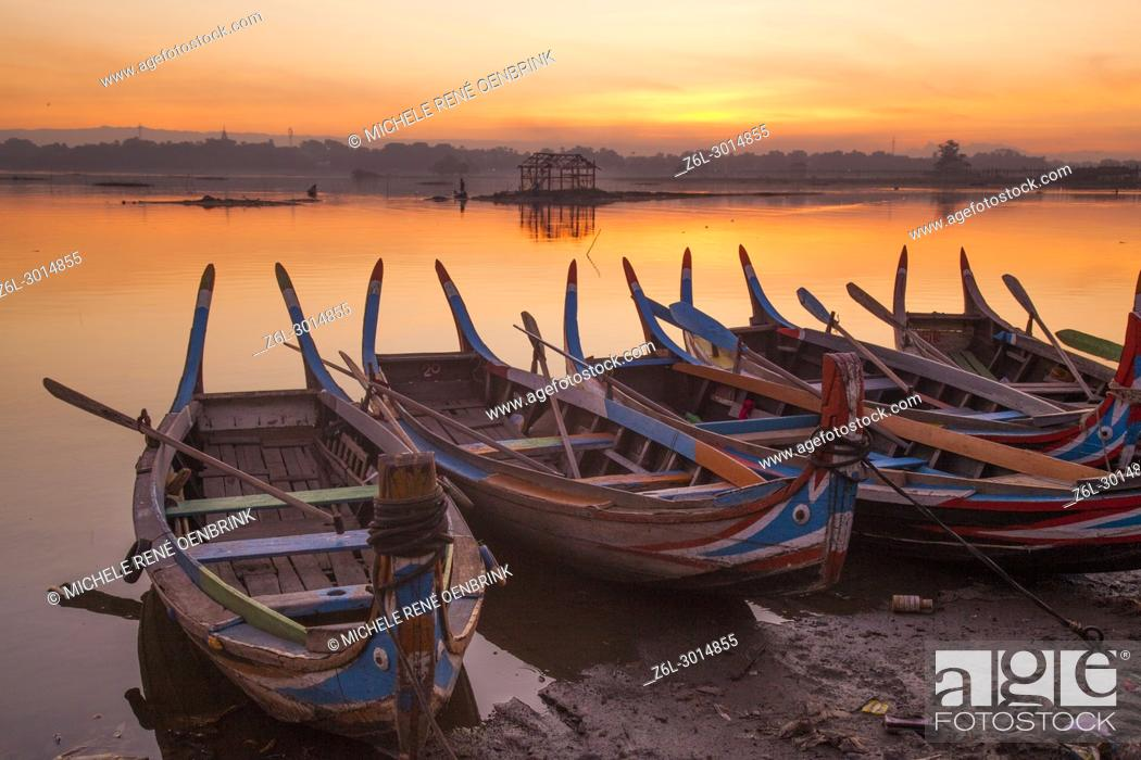 Stock Photo: sunrise over the lake with fishermen on boats fishing in the lake near wooden foot bridge U Bein Bridge crossing the Taungthaman Lake near Amarapura in Mandalay.