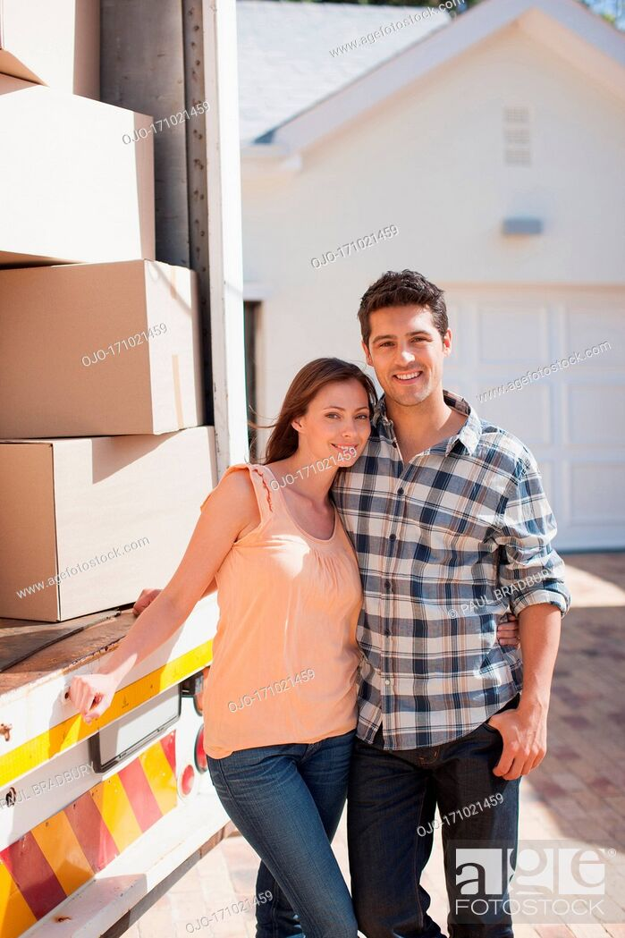 Stock Photo: Couple standing together by moving van.
