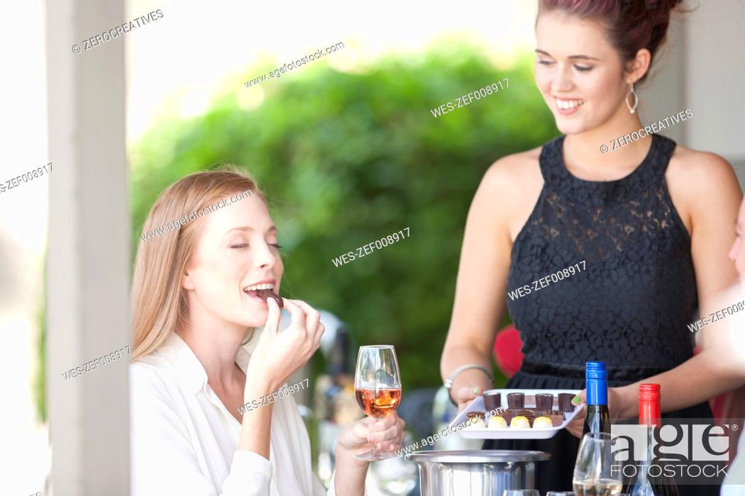 Stock Photo: Woman enjoying wine and chocolates served in restaurant.