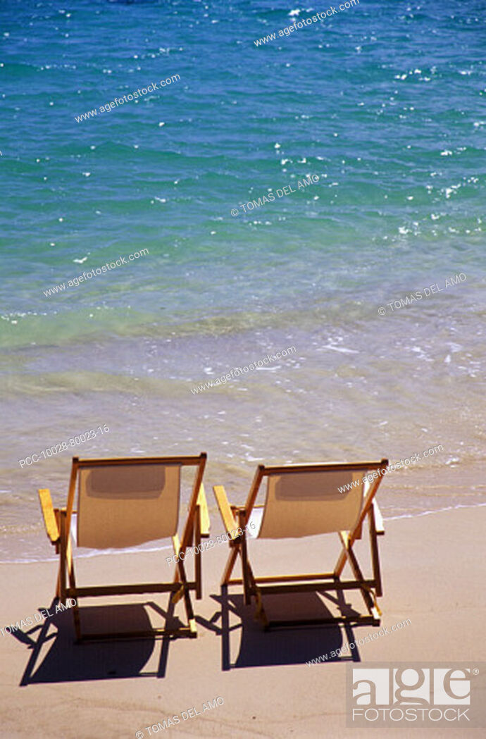 Stock Photo: Beach chairs on the shoreline of a tropical beach, calm waves washing ashore, turquoise water.