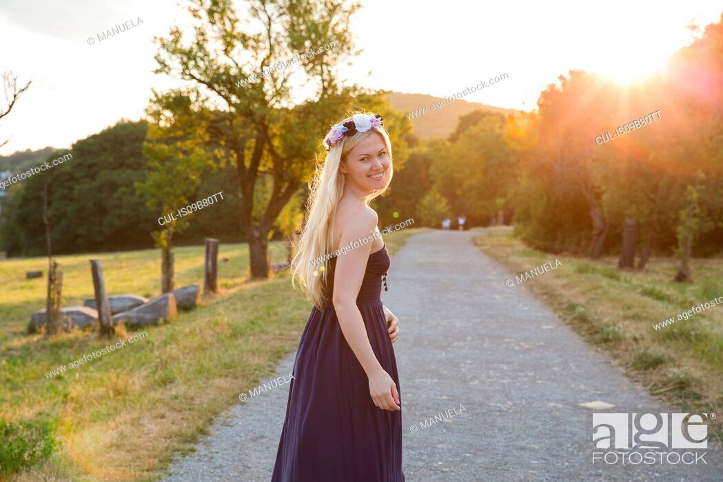 Stock Photo: Woman on rural road wearing strapless dress looking over shoulder at camera smiling.
