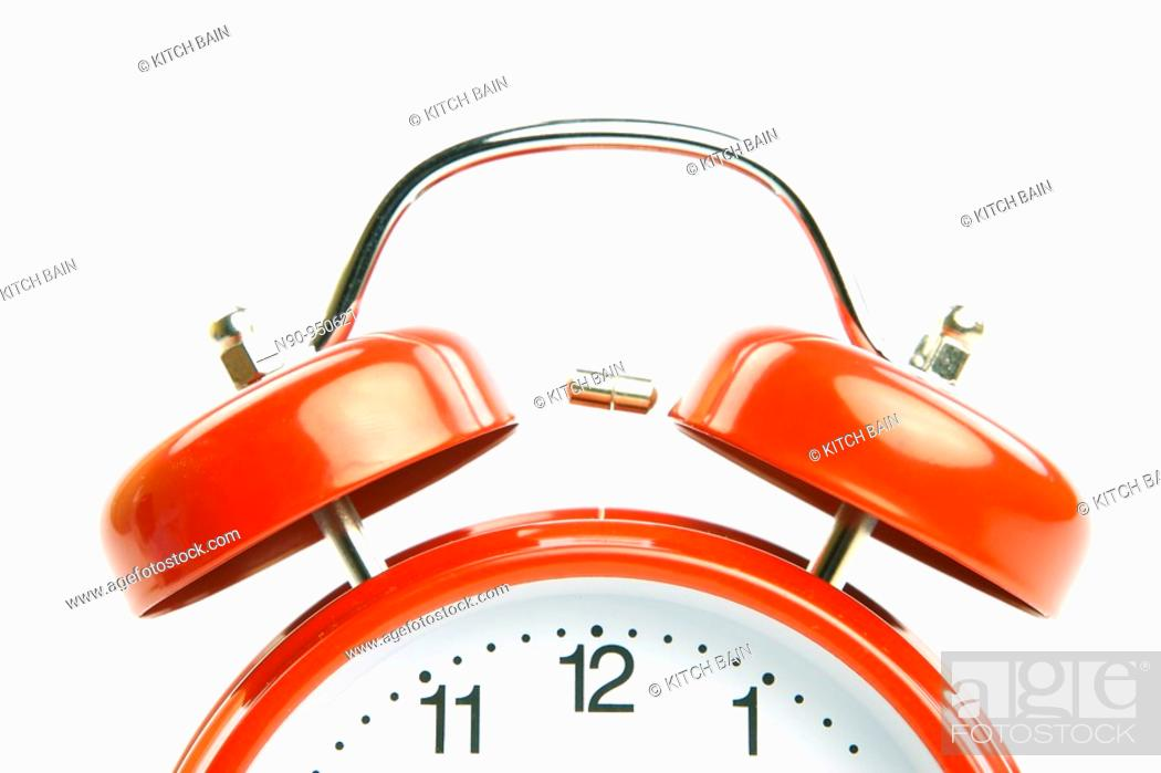 Stock Photo: An old fahion analogue alarm clock set against a white background.