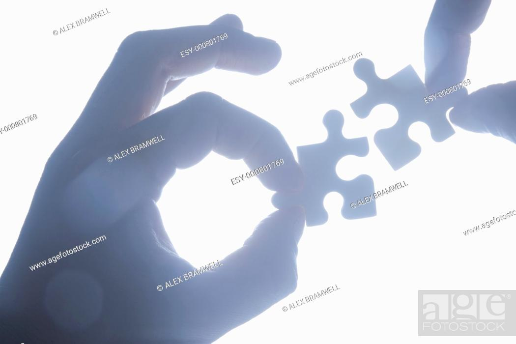 Stock Photo: Hand holding jigsaw piece silhouetted and ijn blue tones.