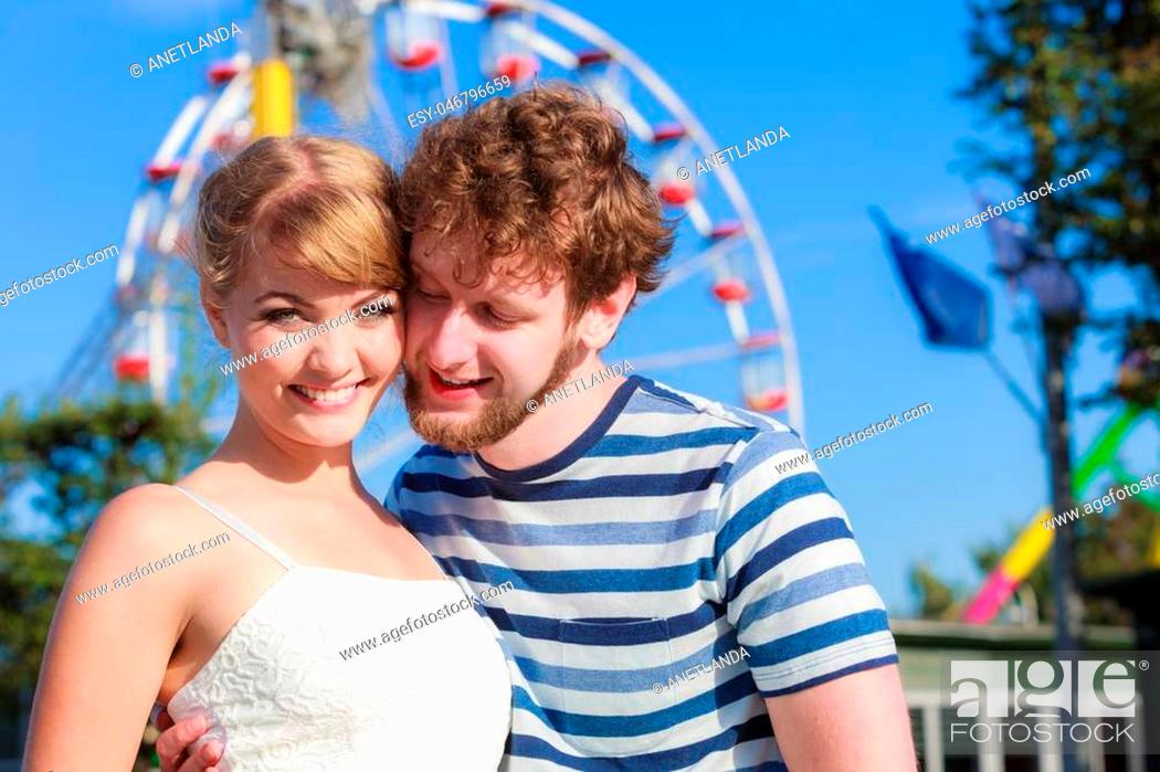 Stock Photo: Summer holidays and happiness concept. Young tourists loving couple outdoor in amusement park ferris wheel in the background.