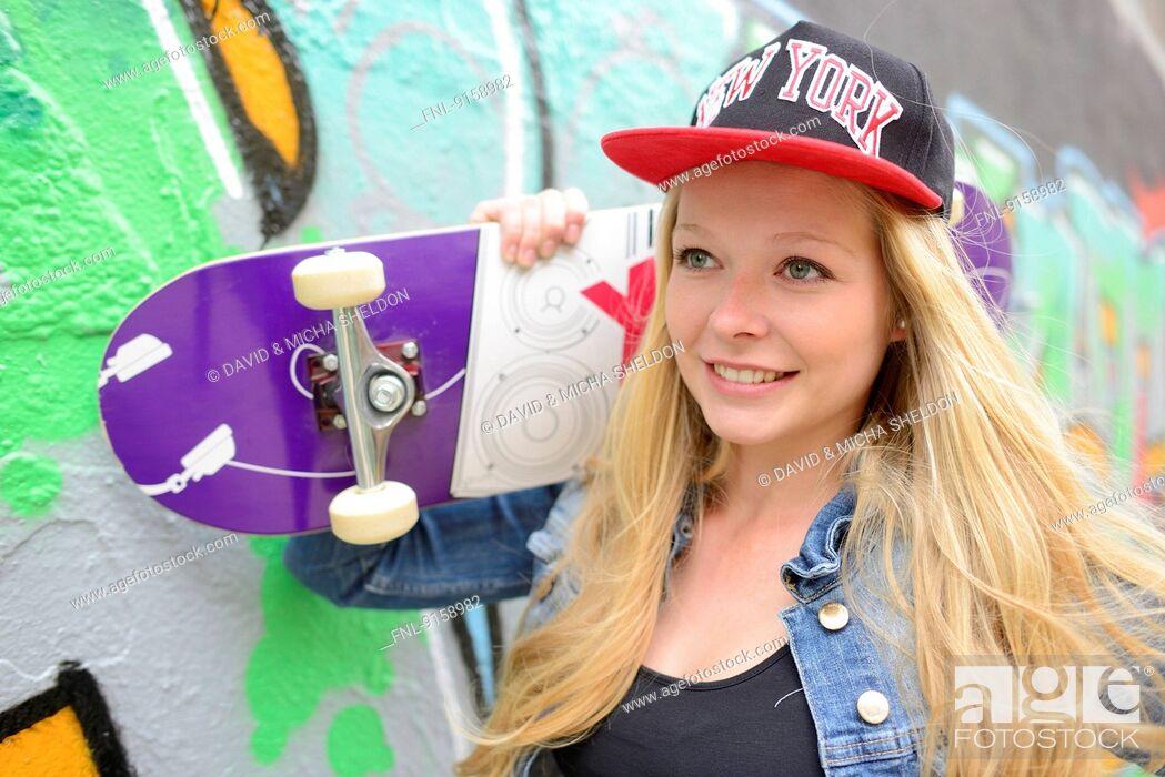 Stock Photo: Young woman at a graffiti wall, Nuremberg, Bavaria, Germany, Europe.