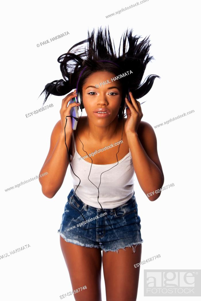 Stock Photo: Beautiful teenager jamming listening to music with wild hair, on white.