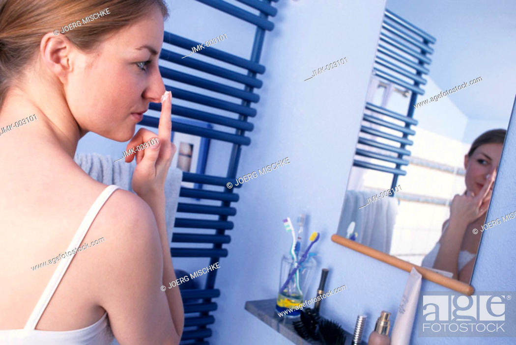Stock Photo: A young woman, 20-25 25-30 years old, in the bathroom, putting cream on her nose in front of a mirror.