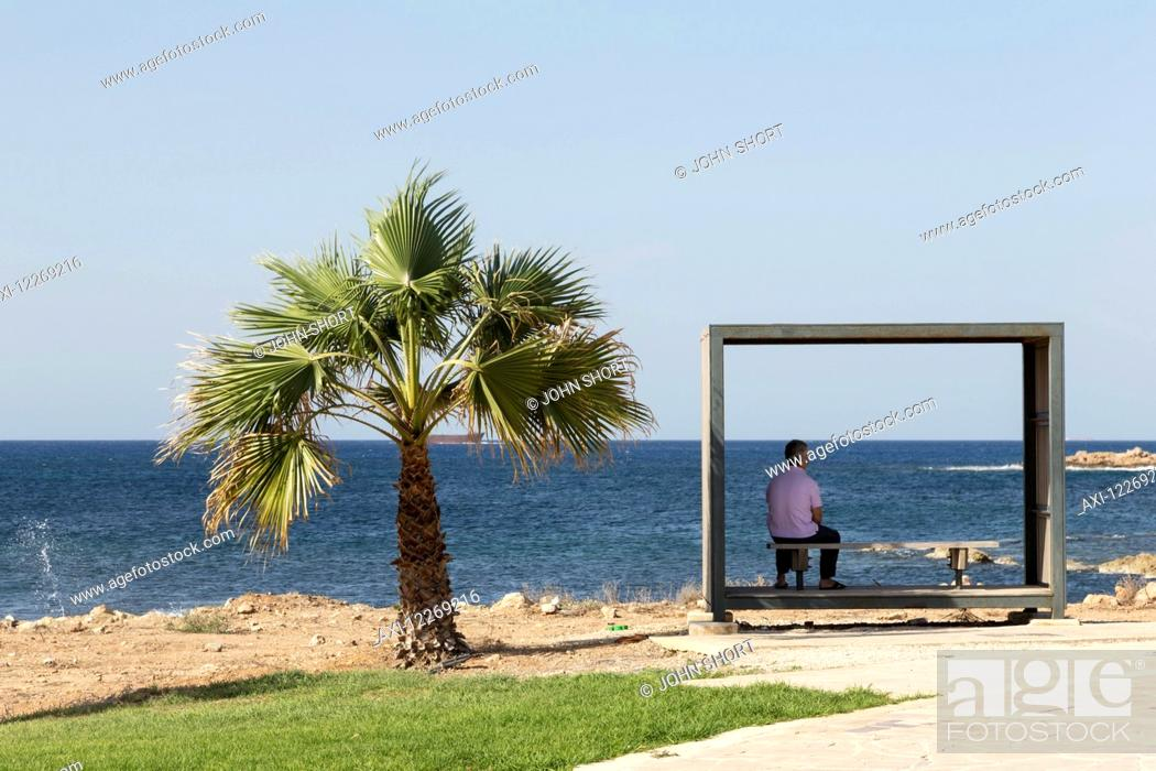 Stock Photo: Man sits in a shaded shelter beside a palm tree at the water's edge; Paphos, Cyprus.