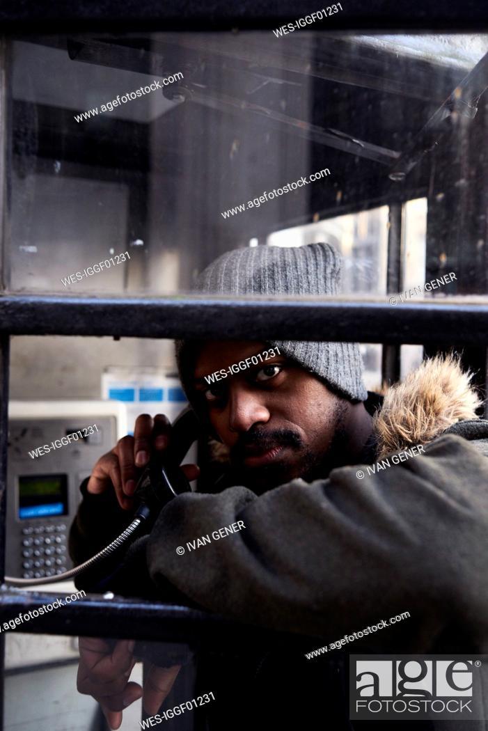 Stock Photo: Mid adult man using a phone box.