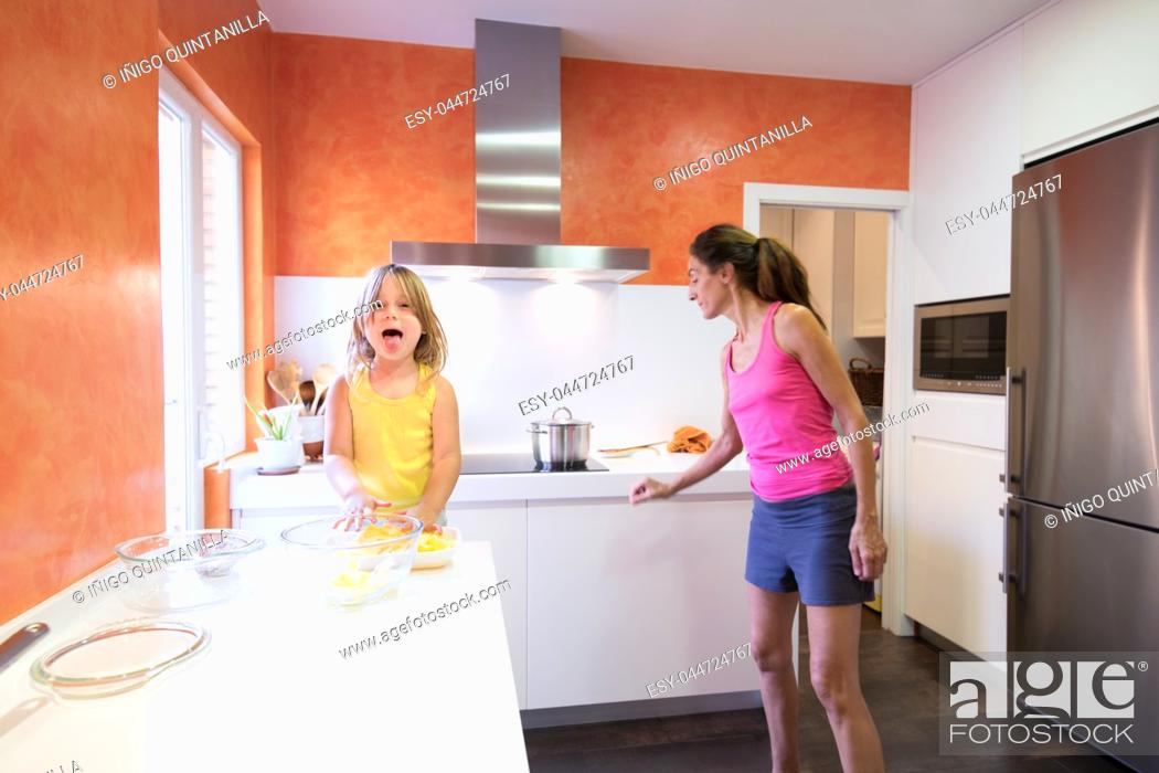 Stock Photo: Four years old blonde happy child preparing raw potatoes to cook in the kitchen, looking and sticking out tongue smiling, next to woman mother.