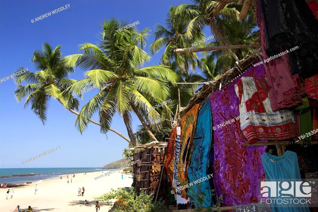 Stock Photo: Coloured fabrics and garments hang beneath palms at beach at the long running weekly Anjuna Flea Market Goa India.