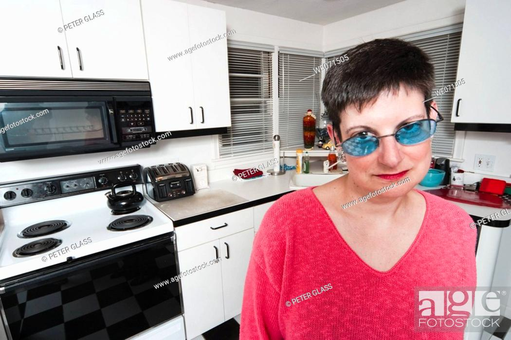 Stock Photo: Woman, wearing sunglasses, posing in her kitchen.