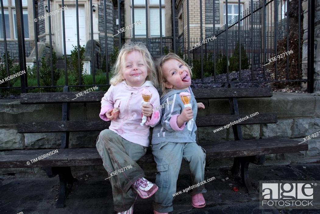 Stock Photo: 6 year and 5 year girls sitting on bench eating icecream and making silly faces.