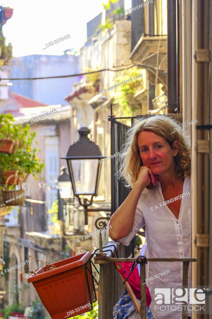 Imagen: Syracuse, Sicily, Italy A Scandinavian tourist stands on a balcony of a B&B.