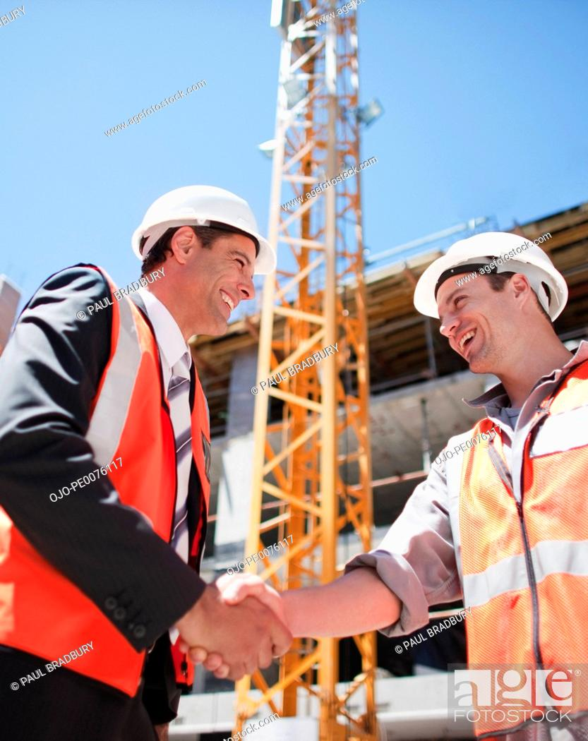 Stock Photo: Construction worker shaking hands on construction site.