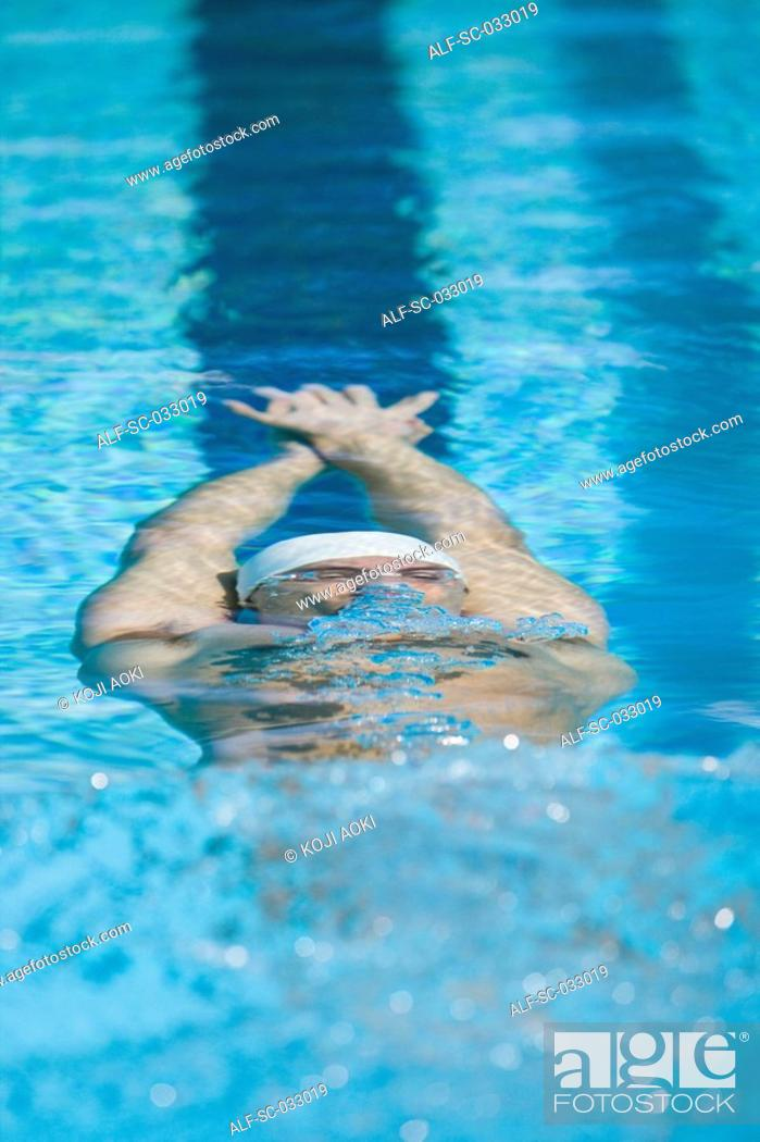 Stock Photo: Young swimmer doing backstroke underwater.