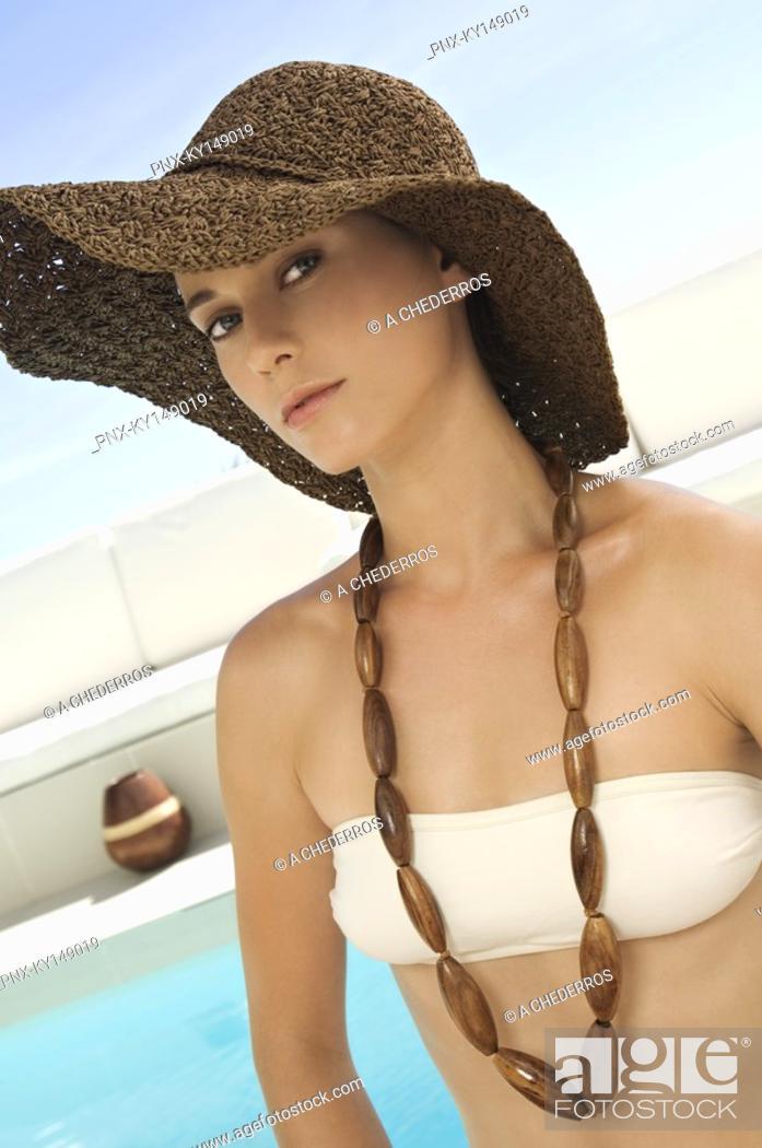 Stock Photo: Portrait of young woman in bikini at pool side.