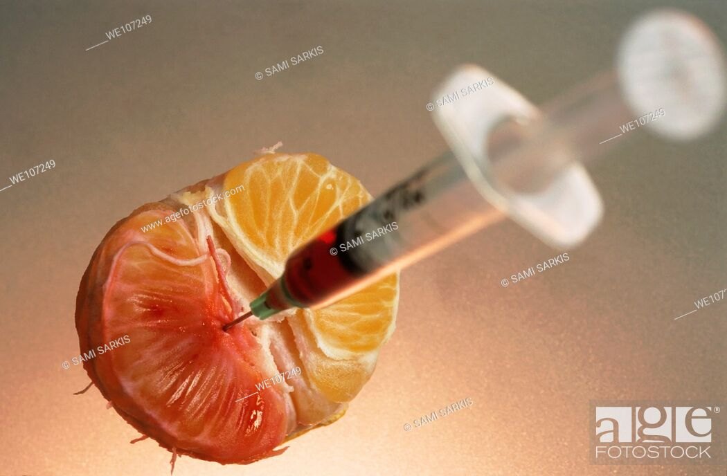 Stock Photo: Syringe needle jabbed into a mandarin showing the possibility of genetically modified food.