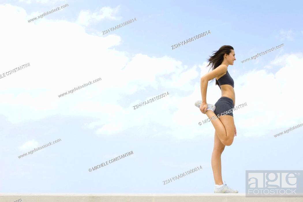 Stock Photo: Young woman in sports clothing standing, holding one foot in hand, side view.