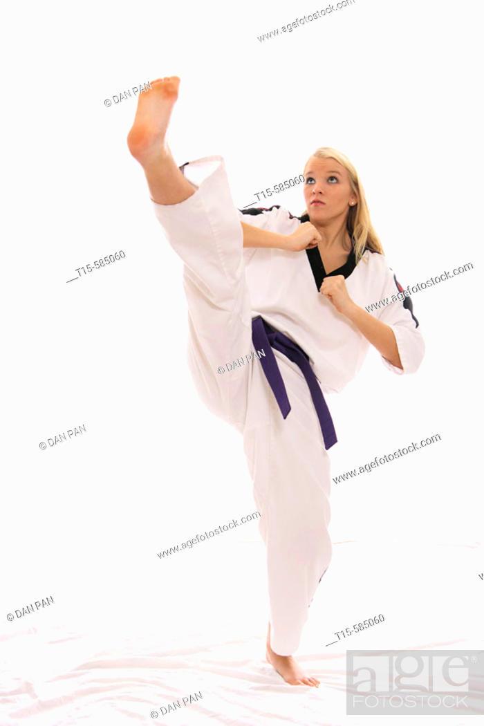 Stock Photo: young woman practice a karate high kick.