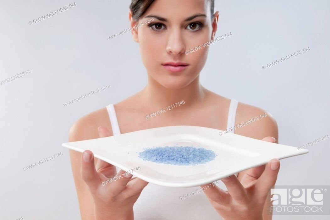 Stock Photo: Portrait of a woman holding a tray of bath crystals.