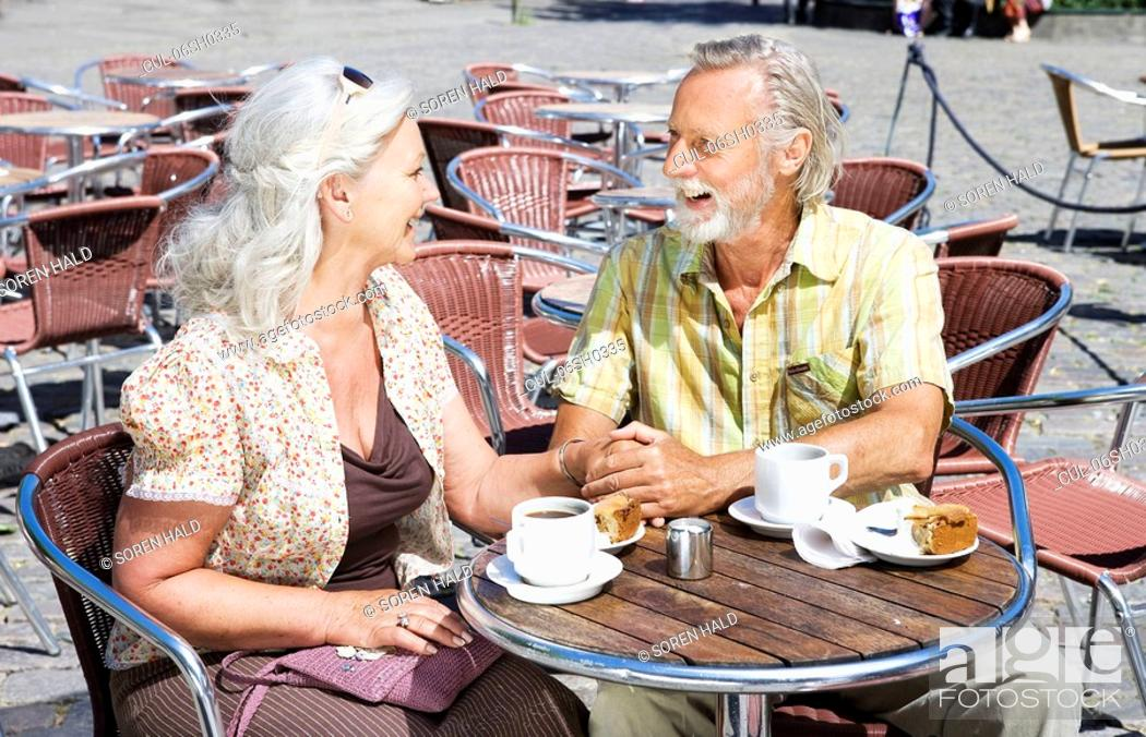 Stock Photo: Couple holding hands by table.